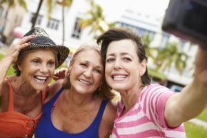 Three Senior Female Friends Taking Selfie In Park